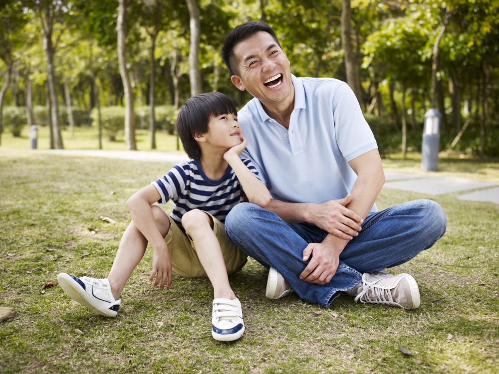 Asian Father Laughing Sitting With Son Outside On Grass