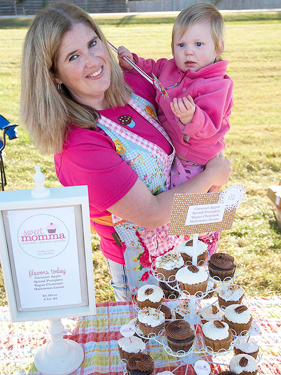 mother holding child at bake sale