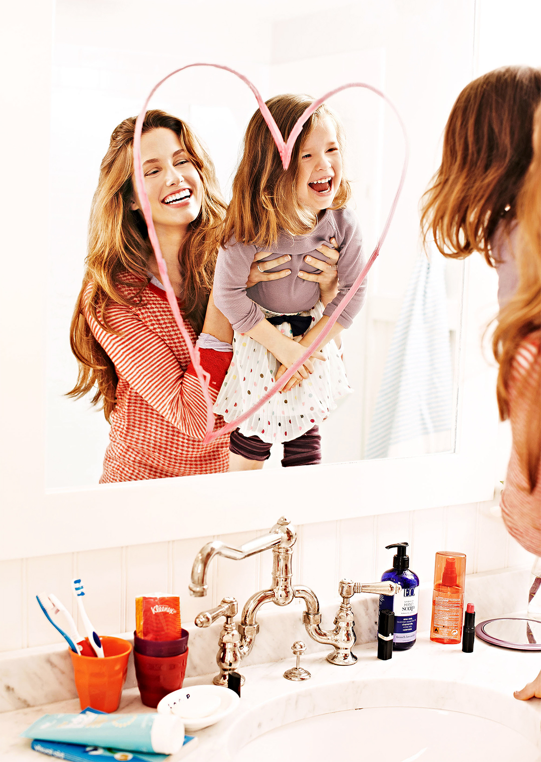 mother and daughter smiling with lipstick heart on mirror