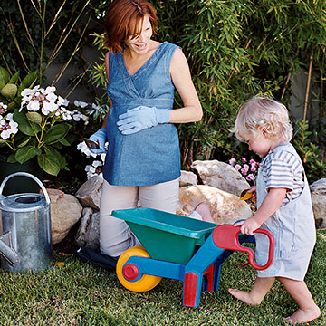 pregnant woman gardening with son