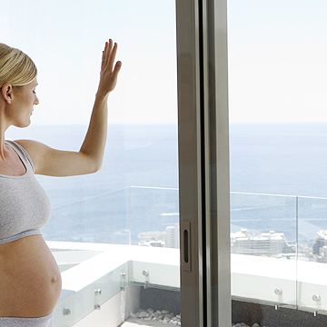 pregnant woman looking out of a window