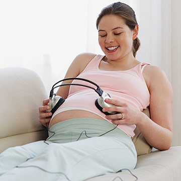 pregnant woman with headphone on belly