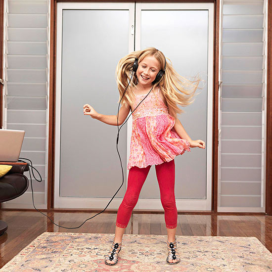 Young girl at home dancing to music