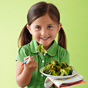 Girl eating broccoli with cheddar cheese