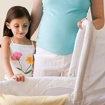 Mother and daughter looking at a crib