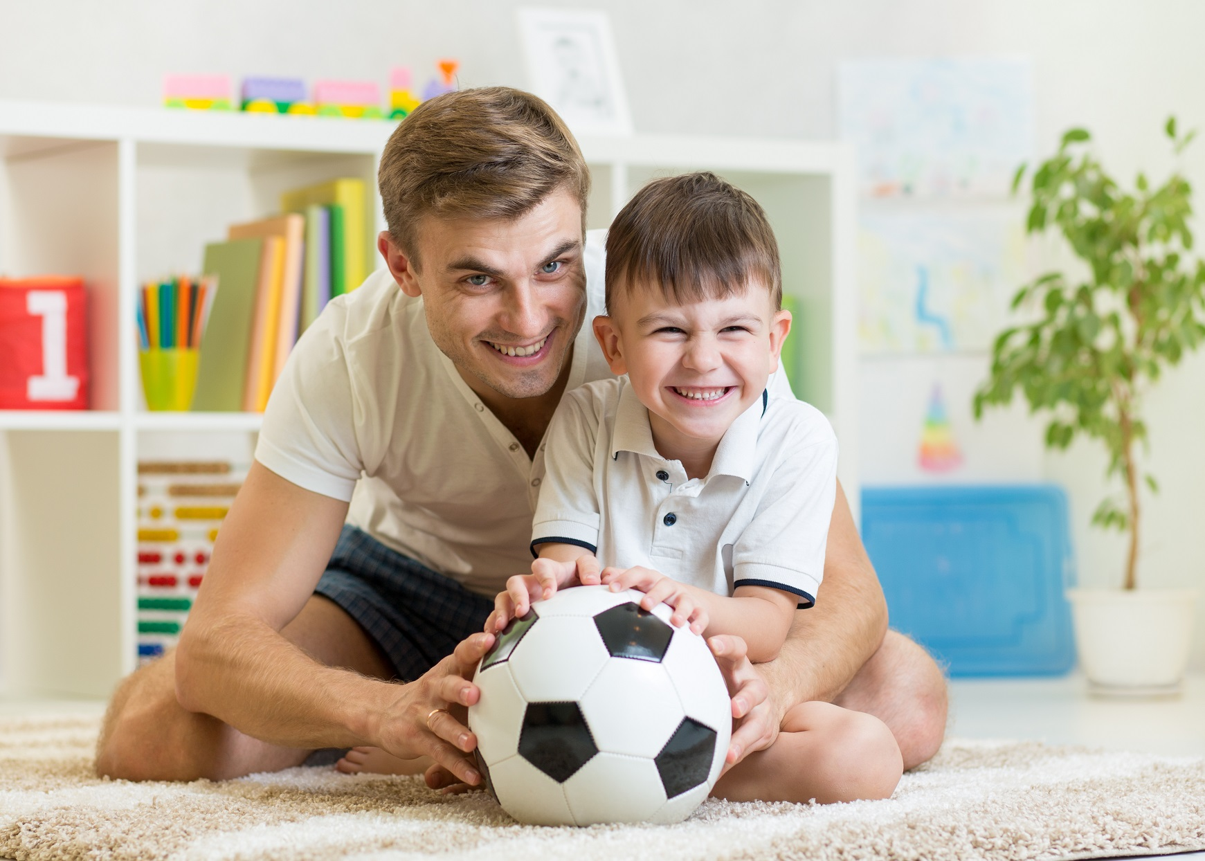 dad and son playing soccer indoors 34975