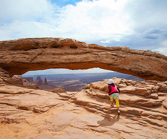 Girl hiking toward arch
