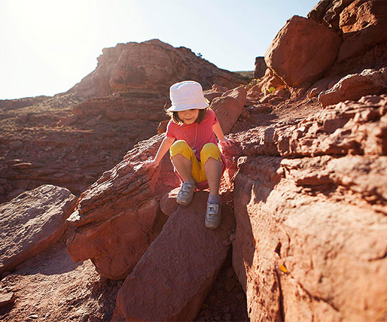Girl in white hat climbing on rocks