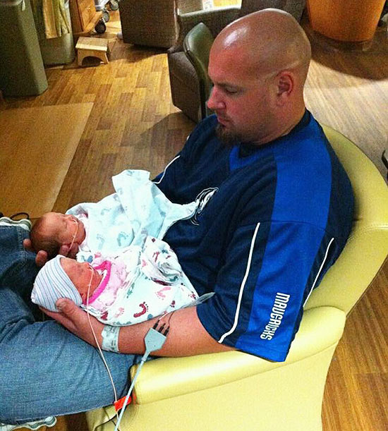 father holding preemie twins