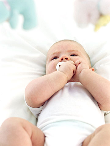 Up close of baby with pacifier, lying down