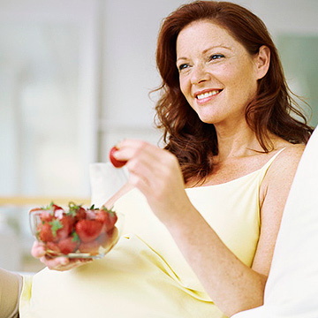 pregnant woman eating strawberries