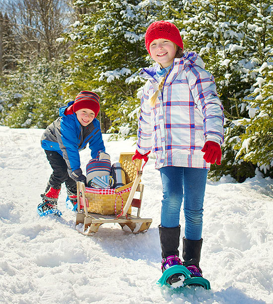 boy and girl in snow with sleds
