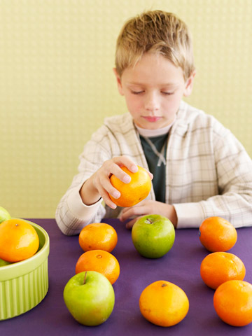 boy learning math with apples and oranges