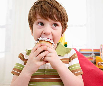 Little boy biting into a cupcake