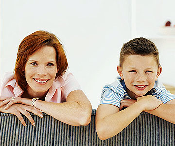 Red haired mom and freckled son smiling while leaning on couch