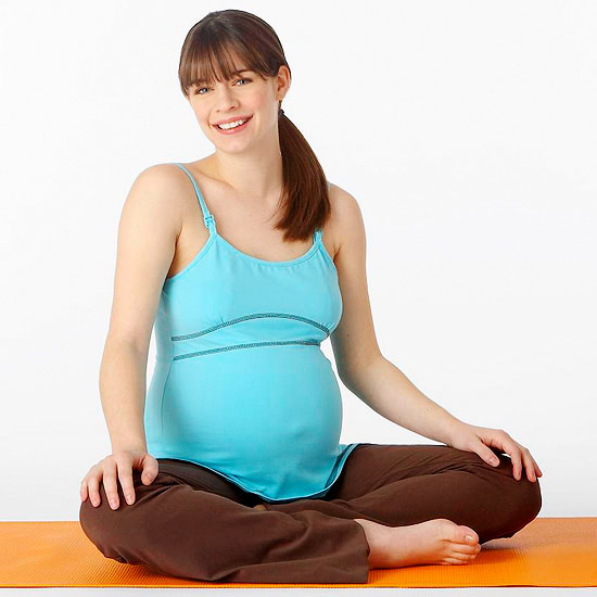 pregnant woman sitting on yoga mat