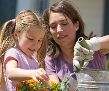 mom helping daughter plant flowers
