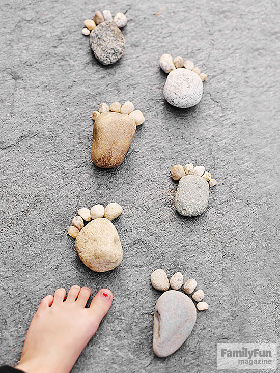 Child's foot and a path of feet shapes made of stones
