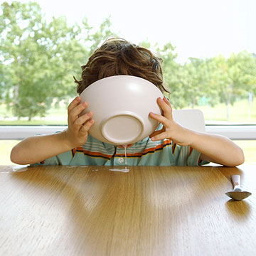 child drinking milk out of bowl
