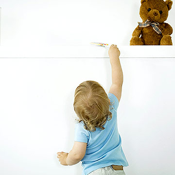 toddler reaching for toy on shelf-1266346276928.xml