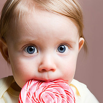 baby girl eating lollipop