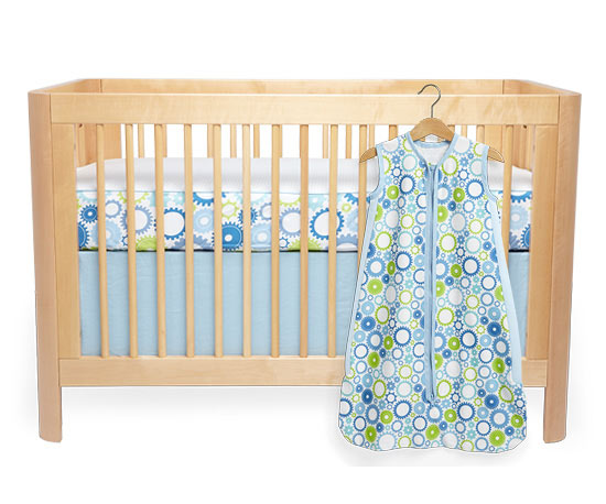 Crib with blue and green patterned sheet