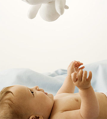 baby looking up at toy