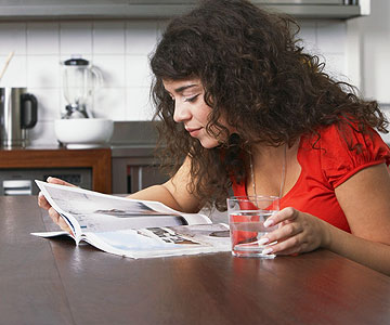 woman reading magazine at table