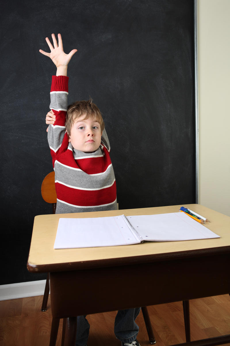 young boy sitting at school desk raising his hand