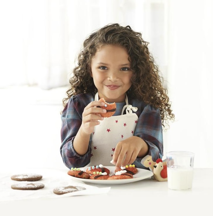 Young Girl with Curly Hair Eating Christmas Cookie
