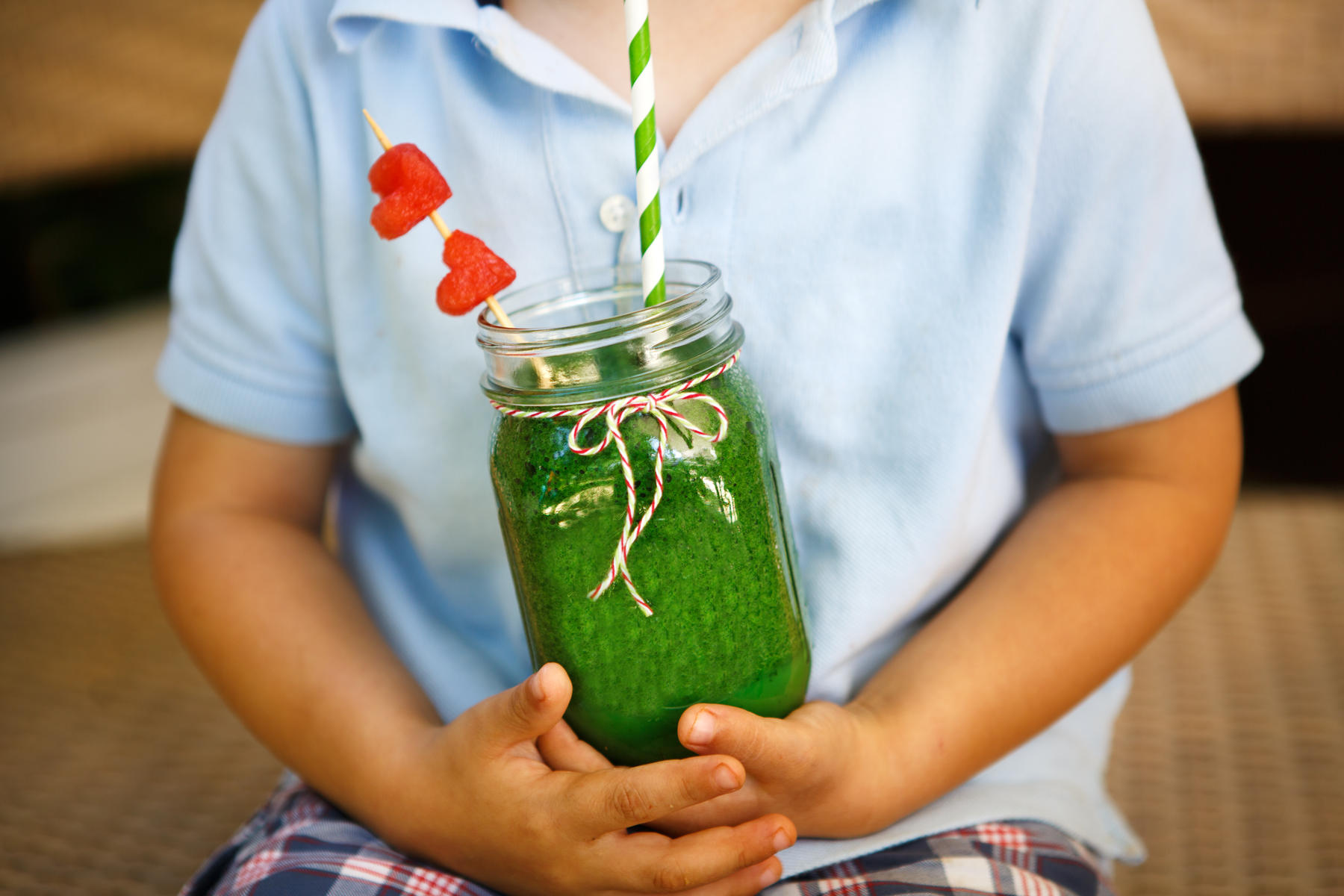 boy holding green smoothie with heart straw