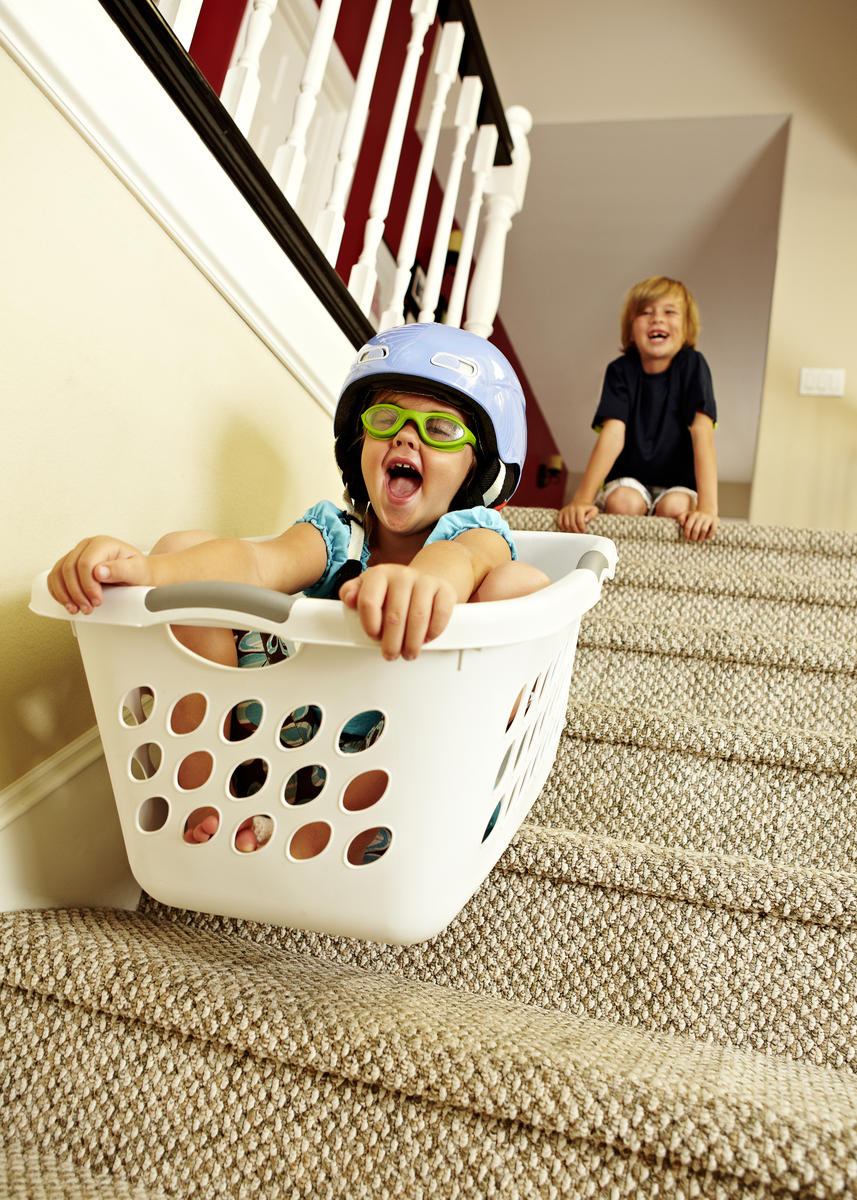 Girl going downstairs in a laundry basket