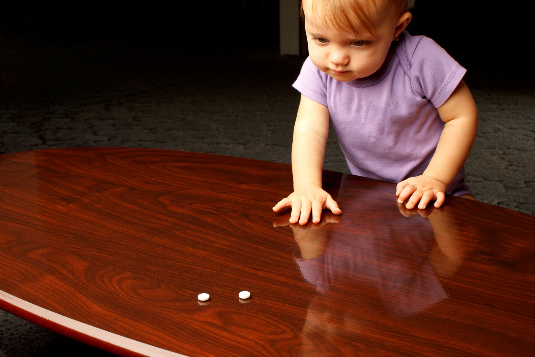 baby with pills on wooden table