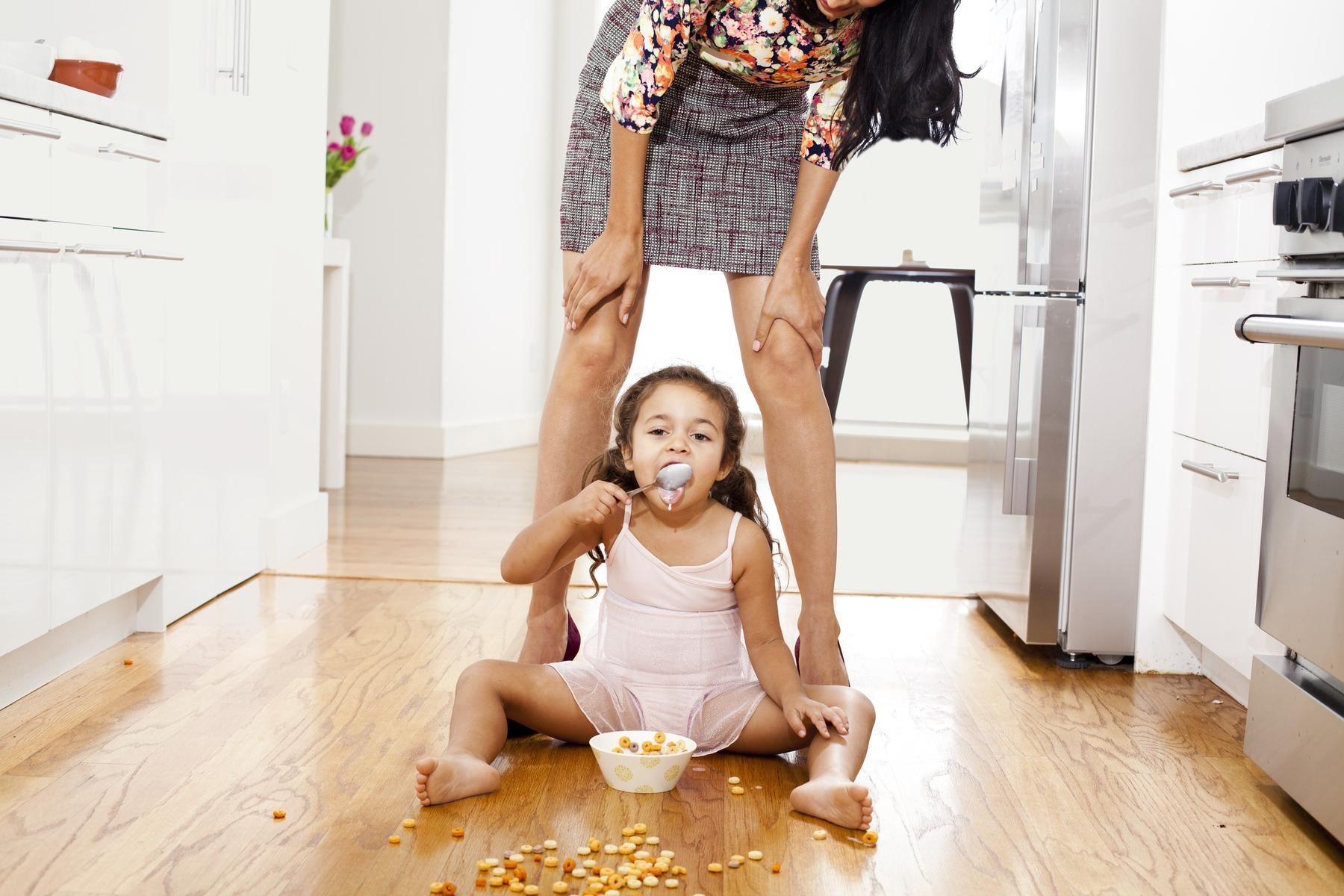 daughter eating cereal and sitting on floor