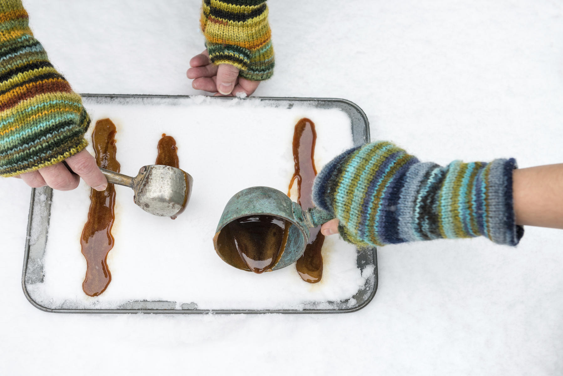 Two People Making Maple Syrup Taffy in Snow