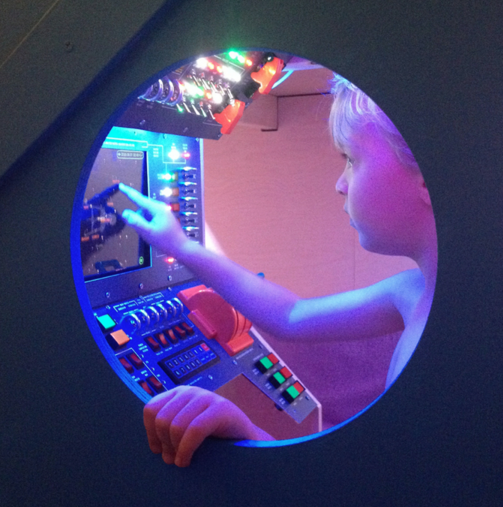 Son at control panel of spaceship loft bed his dad built for him.