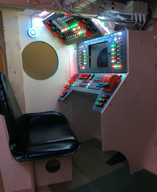 Seat and control panel in spaceship loft bed dad built for son.