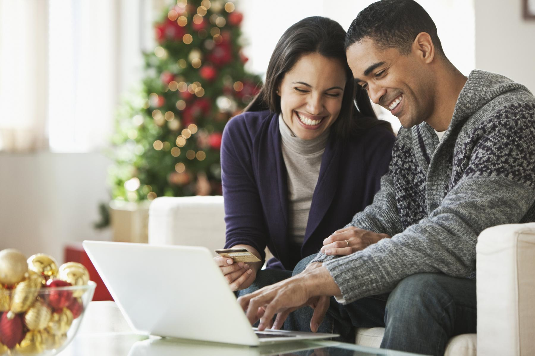 Couple holding credit card and using laptop for holiday shopping