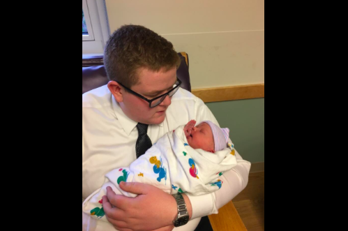 teen in suit holds baby