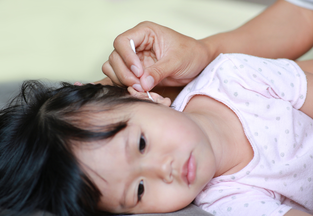 cleaning child's ear with cotton swab