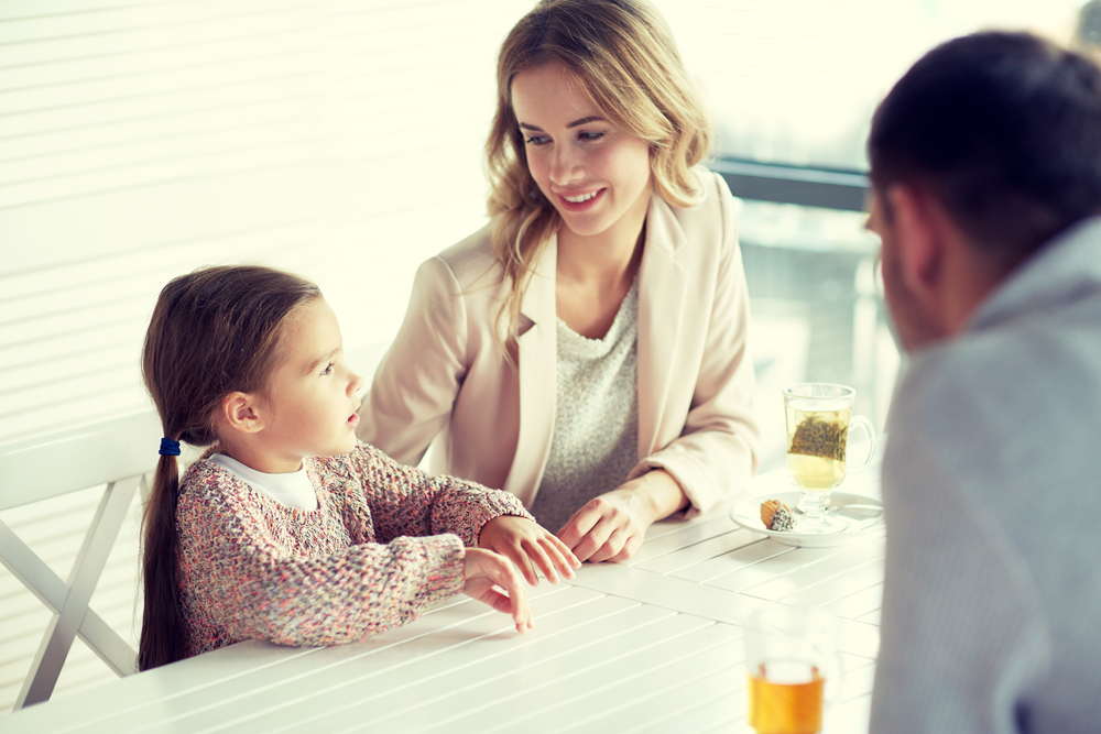 Parents Talking To Daughter At Table