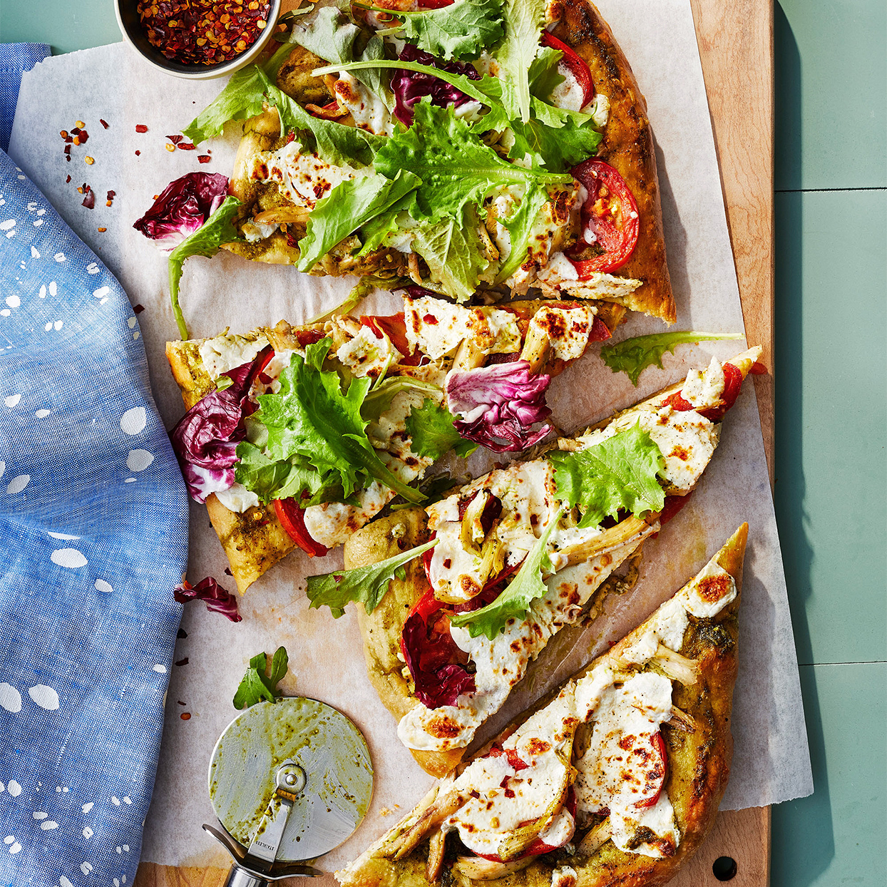 Garlicky Chicken Pizza on cutting board with pizza cutter