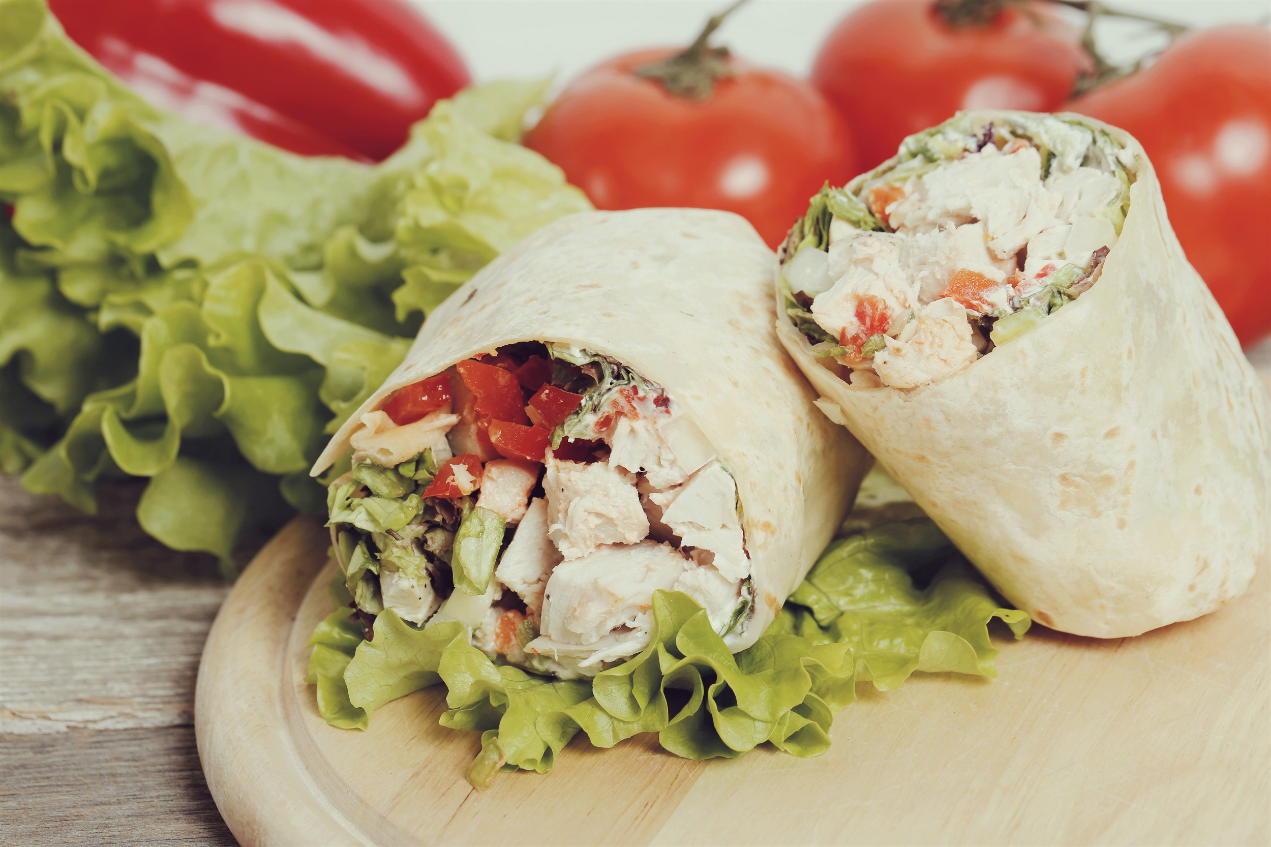 Chicken Wrap Laying on Lettuce and Tomato