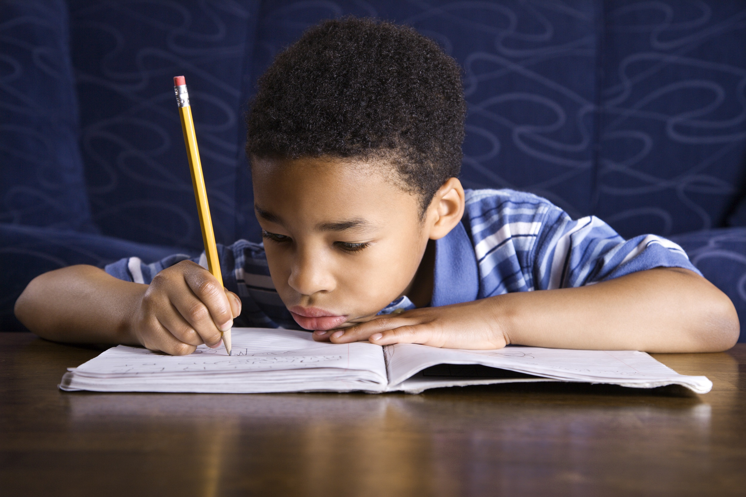 Young African American Boy Writing In Notebook with Pencil