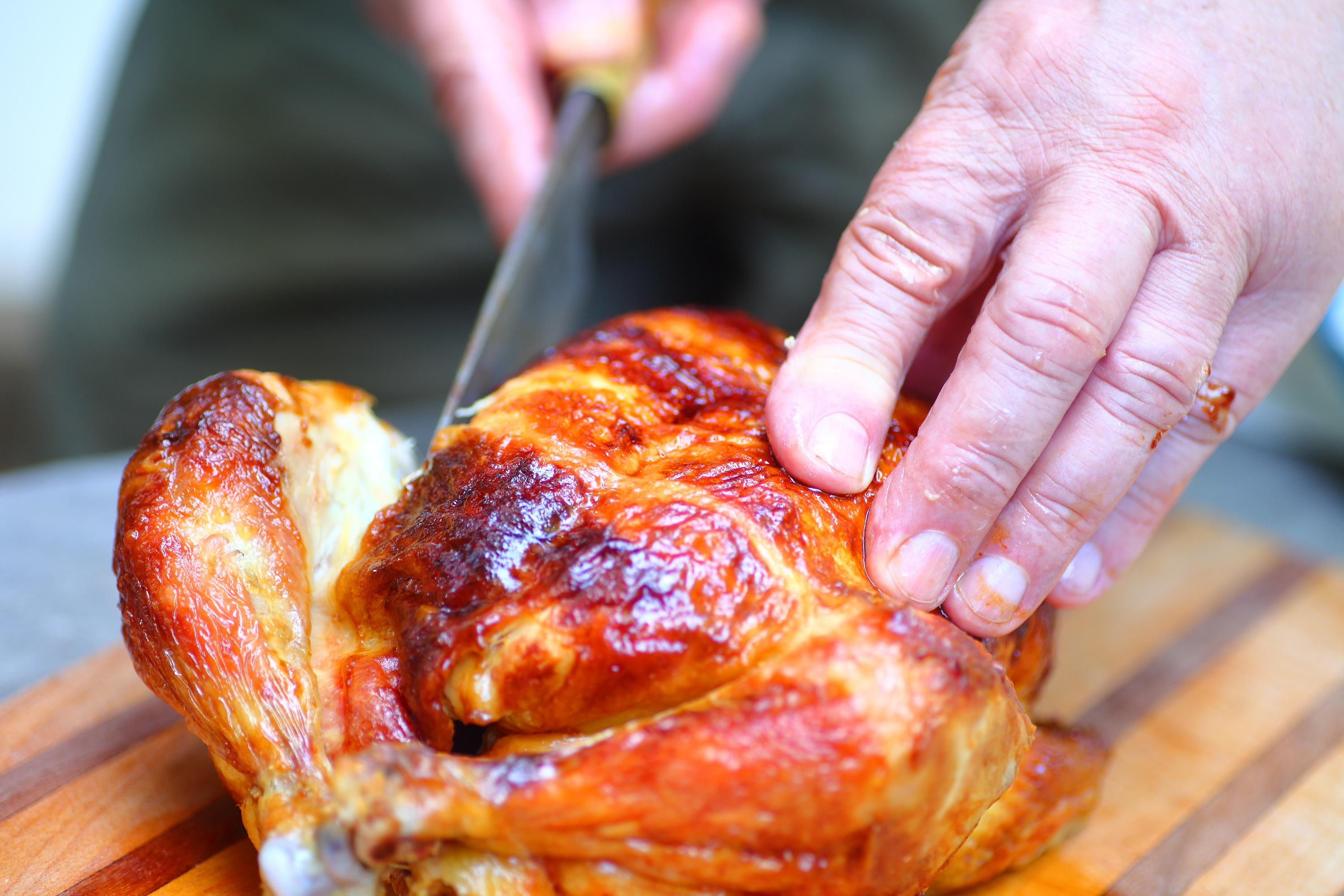 Hands Cutting Rotisserie Chicken on Wooden Cutting Block