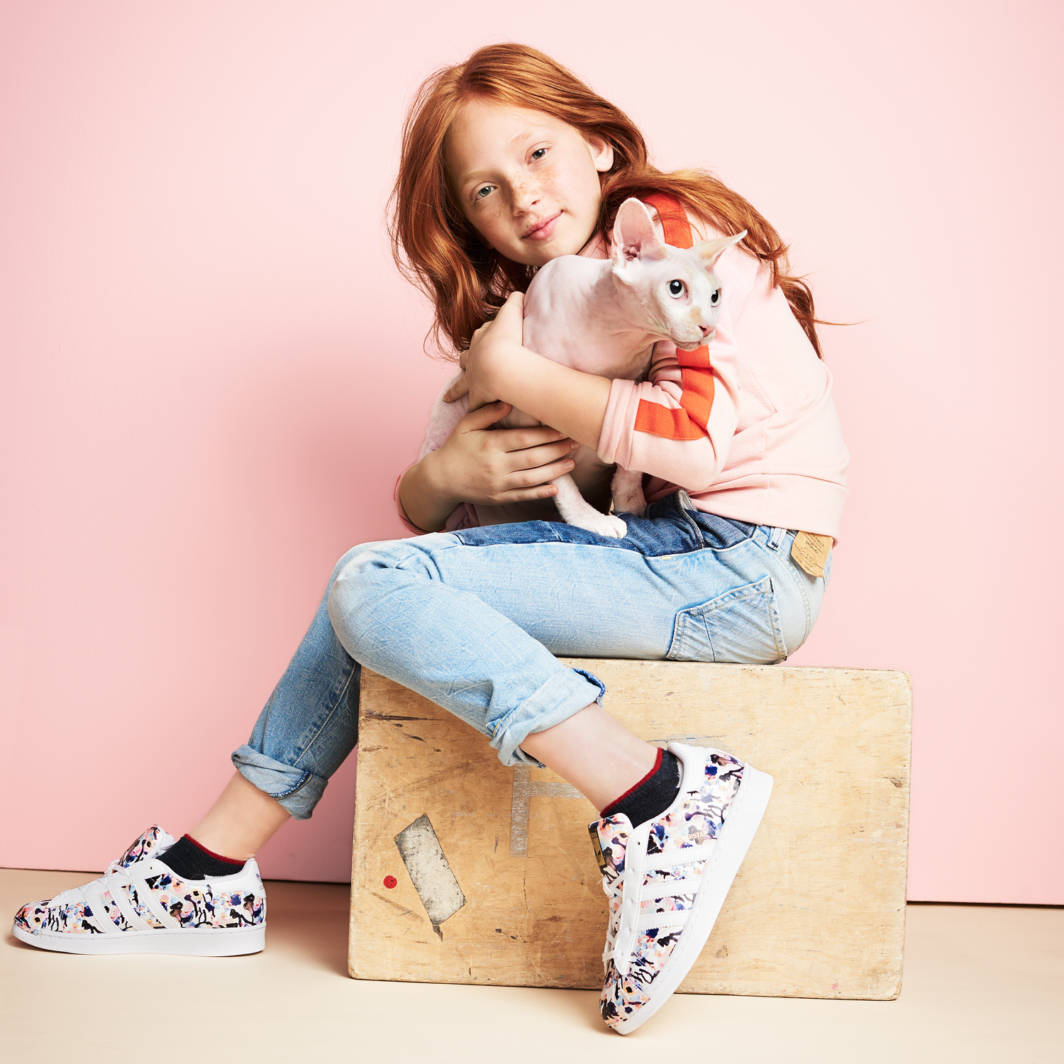 red-haired girl sitting and holding her sphynx cat