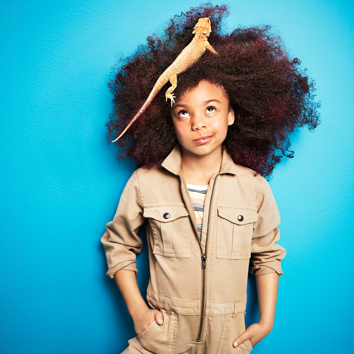 girl wearing jumpsuit with bearded dragon in her hair