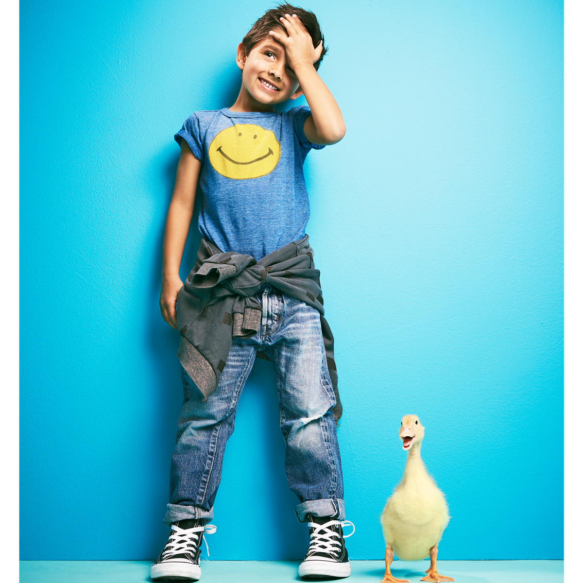 boy in smiley face t-shirt standing next to yellow duck