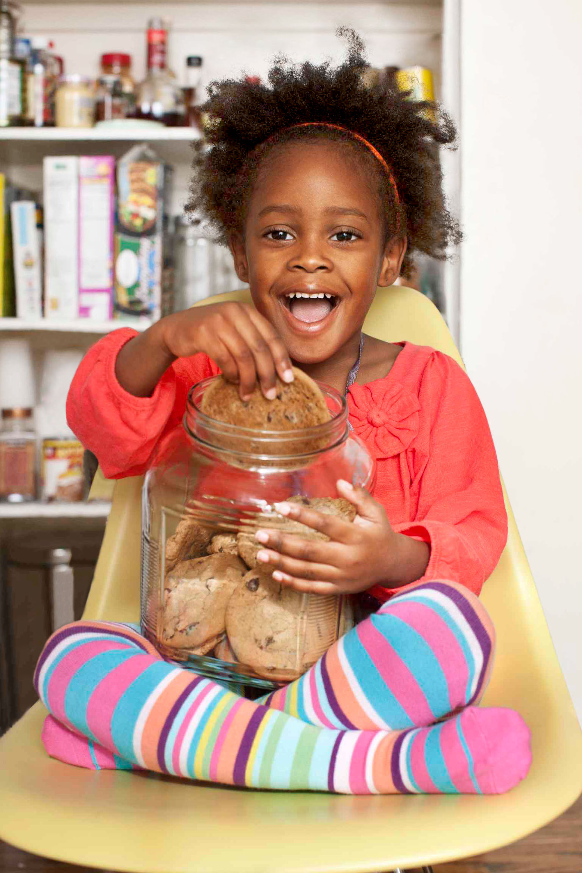 girl with striped leggings grabbing cookie out of jar