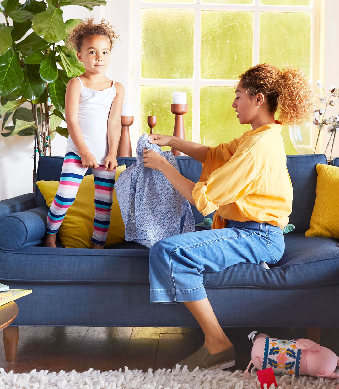 mom looking at daughter's shirt on couch